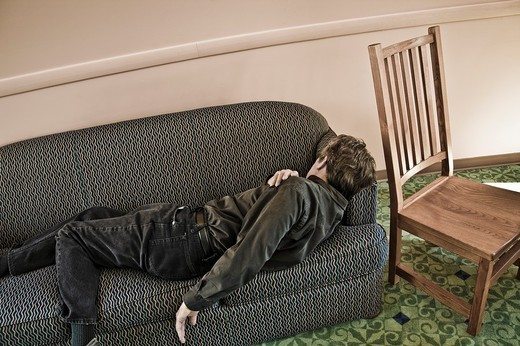 Stock Photo: 1566-618338 Man lying on a sofa in a college lounge