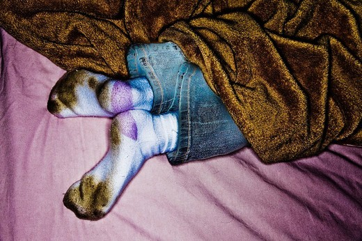 Young girl´s feet sticking out from under her blanket.  Model Released. : Stock Photo