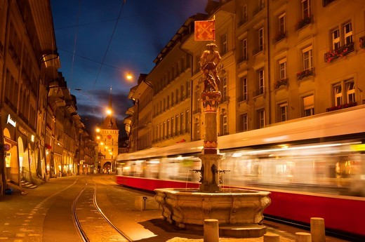 A tram passes by the Musketeer Fountain Schutzenbrunnen on Marktgasse with the Prison Tower Kafigturm in background, Bern, Canton Bern, Switzerland : Stock Photo