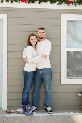 Stock Photo: 1566-620380 A young couple hugging outdoors by a house