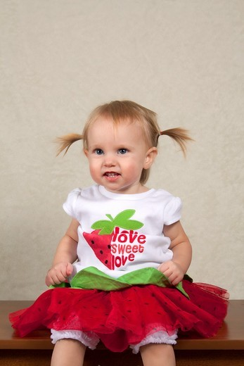 A toddler in a watermelon outift indoors : Stock Photo
