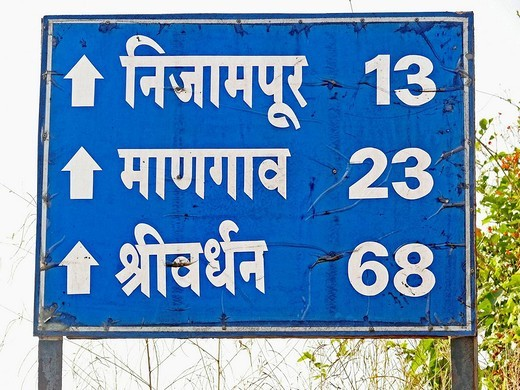 A signboard on a way to harihareshwar is showing distances of Nijampur, Mangaon, Shriwardhan from Wile Village  Maharashtra, India : Stock Photo