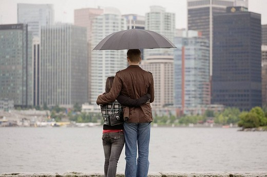 Stock Photo: 1566-624963 A young couple looking at the city skyline under an umbrella on a rainy day, Vancouver, British Columbia, Canada