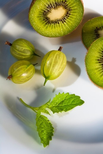 A plate with delicious gooseberries and kiwifruits : Stock Photo