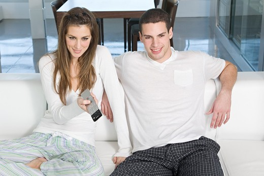 Young couple enjoying leisure time at home watching TV : Stock Photo
