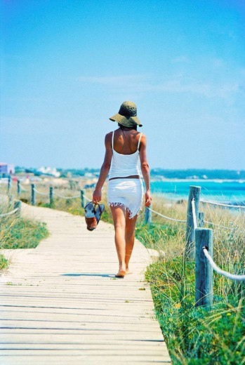 Stock Photo: 1566-626456 Back view of a woman walking by the sea