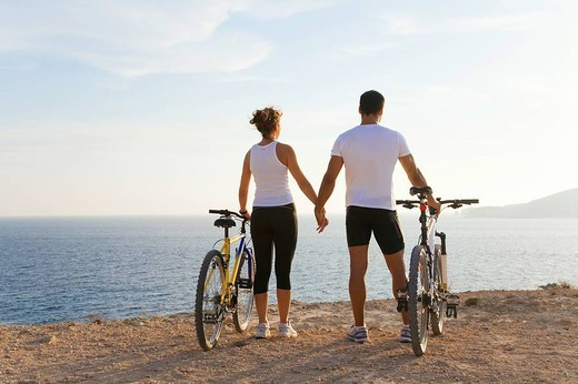 Stock Photo: 1566-626512 Rear view of a couple with bikes in a cliff