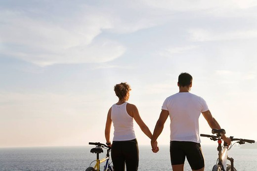 Stock Photo: 1566-626513 Rear view of a couple with bikes by the sea