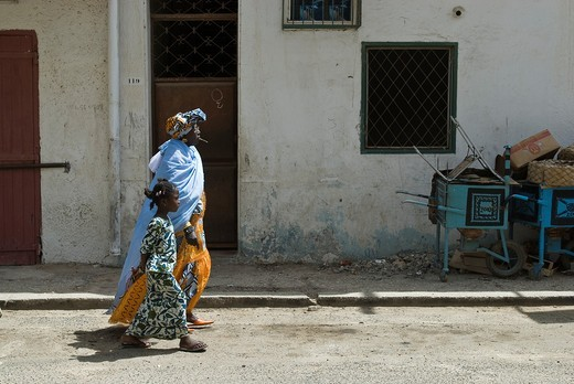 Stock Photo: 1566-629020 Old woman and girl with traditional clothes walking on the street, Saint-Louis, Senegal, Africa