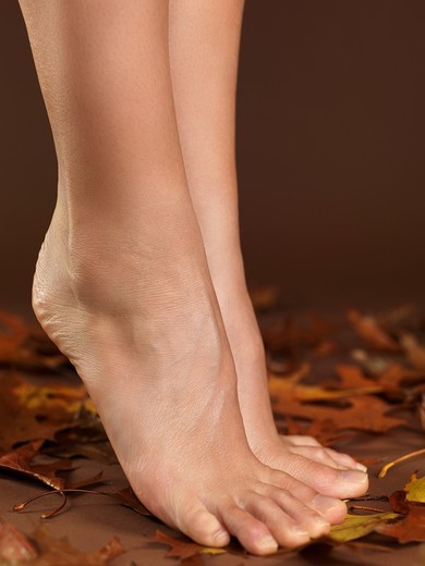 Stock Photo: 1566-629639 Closeup of legs of a woman standing barefoot on autumn leaves