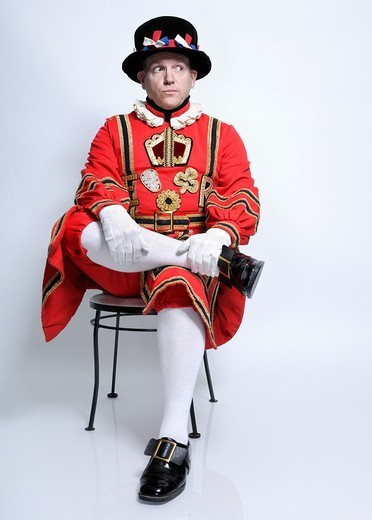 Stock Photo: 1566-629710 Royal Bodyguard - Beefeater - The Yeomen Warder sitting on a chair and looking sideways at the copyspace  Isolated portrait on white background