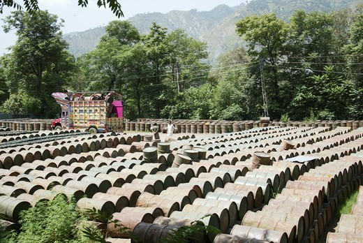 Barrels lined up in Pakistan  An earthquake hit Pakistan in October 2005, destroying hundreds of villages and claiming thousands of lives  Emergency relief efforts struggled to help the survivors of this disaster amid harsh living conditions, difficult te : Stock Photo