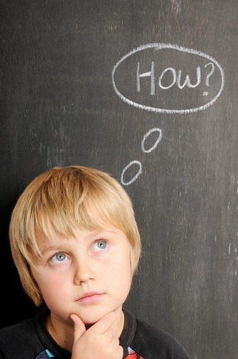 Stock photo of a young boy in fornt of a blackboard with chalk thought bubbles spelling the word how : Stock Photo