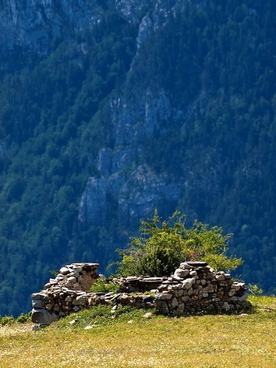 Stock Photo: 1566-636736 Borda in ruins and meadows with the Rock of St. Martin in the background - The Commune - Gistaín Valley - Sobrarbe - Aragon Pyrenees - Huesca - Aragón - Spain