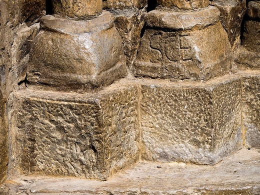 Bases of columns with a carved epigraph, main front of the Romanesque collegiate church of Santa Maria (12th century), Ainsa. Sobrarbe, Huesca province, Aragon, Spain : Stock Photo