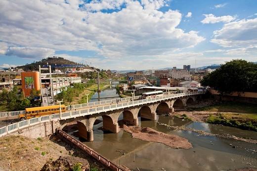 Stock Photo: 1566-637485 Honduras, Tegucigalpa, Buses crossing Bridge over Rio Choluteca, Mercada La Isla, La Isla Market, National stadium, Estadio Nacional, Tiburchio Carias Andino, and Parque La Paz