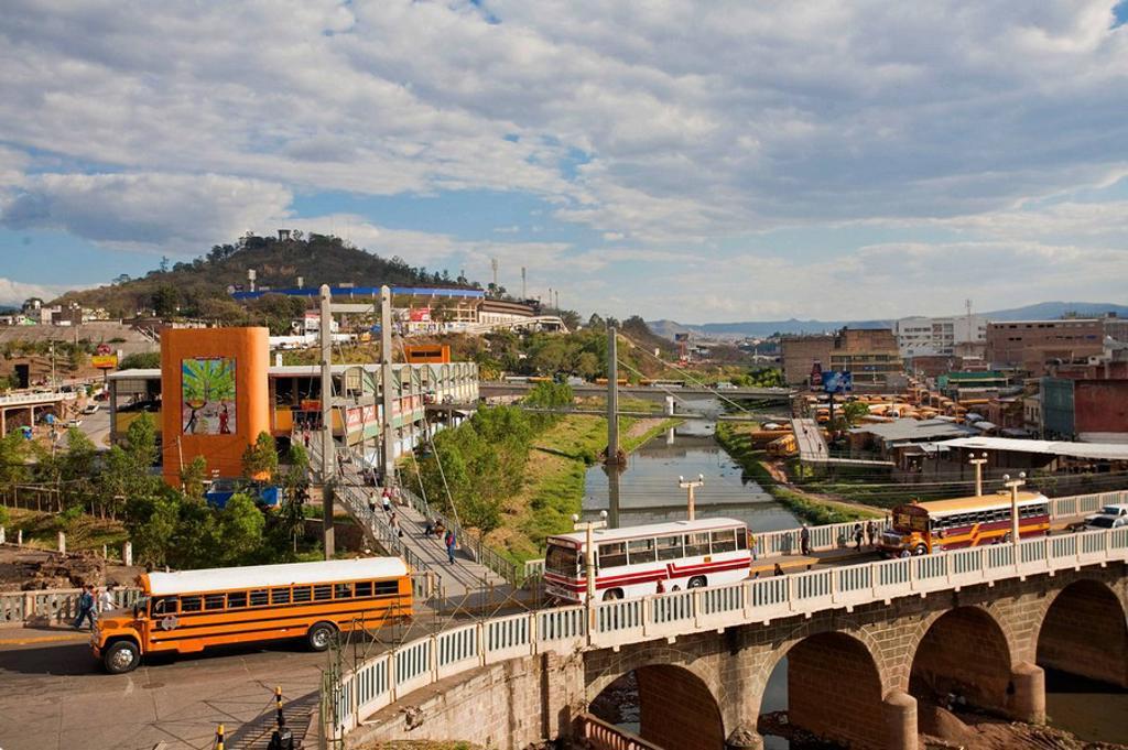 Honduras, Tegucigalpa, Buses crossing Bridge over Rio Choluteca, Mercada La Isla, La Isla Market, National stadium, Estadio Nacional, Tiburchio Carias Andino, and Parque La Paz : Stock Photo