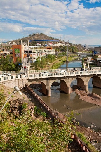 Stock Photo: 1566-637489 Honduras, Tegucigalpa, Buses crossing Bridge over Rio Choluteca, Mercada La Isla, La Isla Market, National stadium, Estadio Nacional, Tiburchio Carias Andino, and Parque La Paz