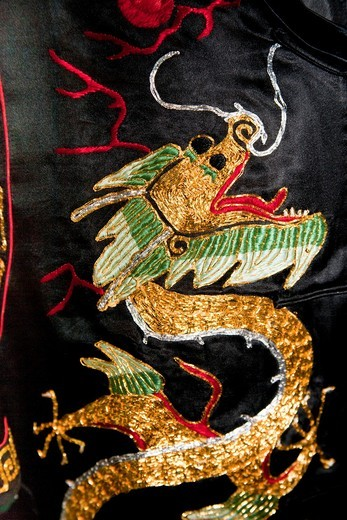Black, gold and red Chinese embroidered silk garment depicting a dragon, for sale, China : Stock Photo