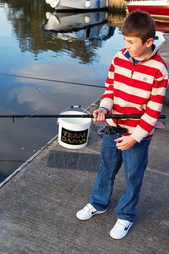 A MODEL RELEASED picture of a ten year old boy fishing in a river in the Uk : Stock Photo