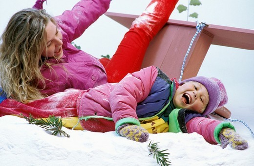 mother and daughter enjoying crashing their sled in the snow : Stock Photo