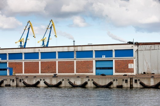 Harbor at the baltic sea with freight house and two cranes and industrial buildings in the background. Shot in the Hanseatic city of Wismar, Germany. : Stock Photo