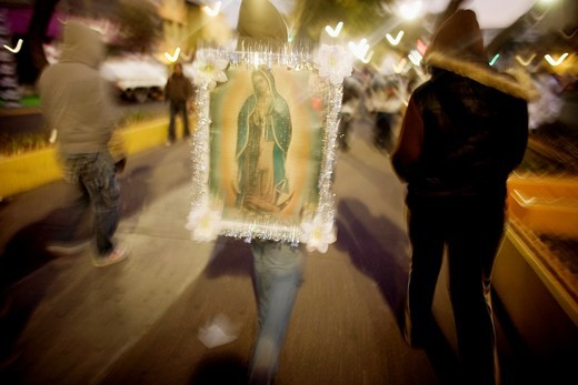 A pilgrim carries an image of the Our Lady of Guadalupe outside of the Our Lady of Guadalupe Basilica in Mexico City, December 11, 2010  Hundreds of thousands of Mexican pilgrims converged on the Basilica, bringing images to be blessed, as processions fil : Stock Photo