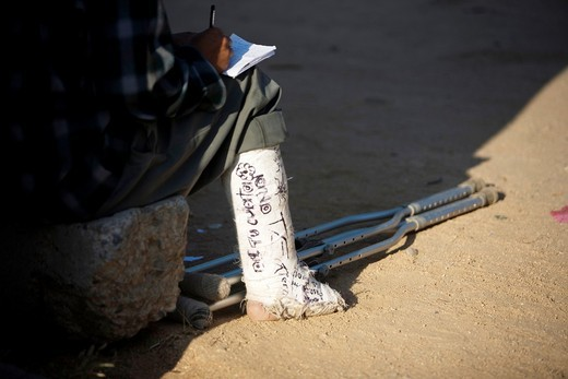 Stock Photo: 1566-642904 A Central American migrant traveling across Mexico to work in the United States with a plastered leg rests at the Catholic priest Alejandro Solalinde´s shelter Hermanos del Camino Brothers of the road located along the railroad, 300 kilometers from the Me