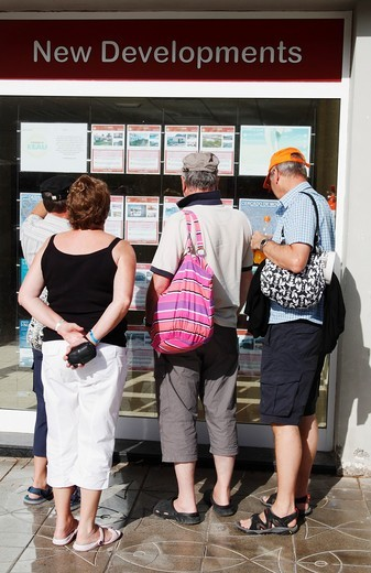 Tourists looking at Estate agents window in Puerto de Mogan, Canary Islands, Spain : Stock Photo