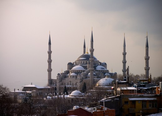 Stock Photo: 1566-642994 Shy sunrise in winter on the snowy Sultan Ahmed Mosque Turkish: Sultanahmet Camii also called blue mosque, Istambul, Turkey, with the fogy Bosphorus in the back