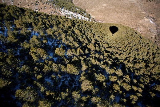The shadow of our globe view from the air above the trees in the Sierra de Baza partially snow : Stock Photo
