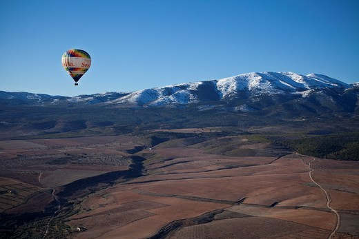 Stock Photo: 1566-644578 An air balloon at sunset flying over fields of Granada to the Sierra de Baza