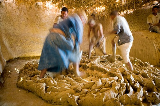 Stock Photo: 1566-648667 Men kneading argil with their foot while singing raucously in a weird choregraphy. Ancestral pottery workshop near Maruza, between Qena and  Luxor, using locally extract argile. Egypt