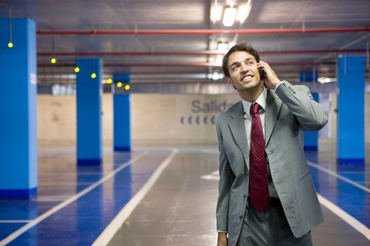 Businessman with mobile phone. Parking lot. : Stock Photo