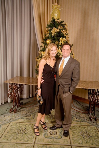 An attractive young couple pose for a formal picture in front of a Christmas tree at a hospital emergency room staff´s holiday party in Orange, CA. : Stock Photo