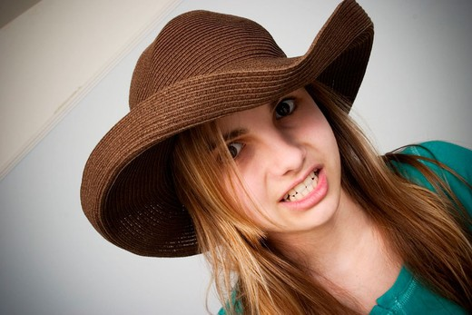 Long blond-hair teen girl wearing a hat : Stock Photo