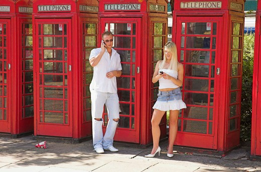 Young couple using mobile phones on street next to row of British public phone boxes. : Stock Photo