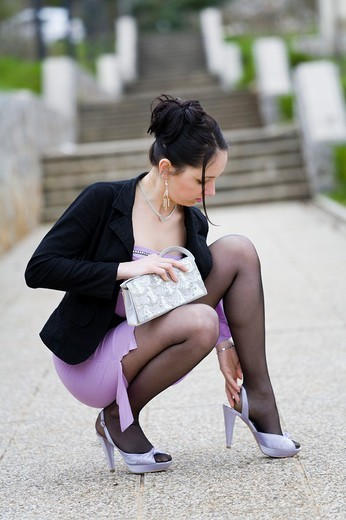 Young woman is squatting on the street and adjusting a shoe : Stock Photo
