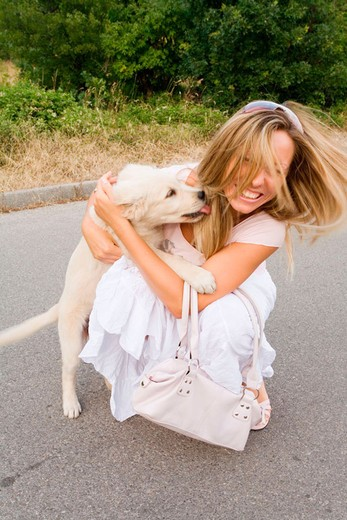 Her pet dog is licking young woman affectionately : Stock Photo