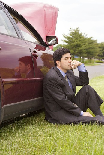 Stock Photo: 1566-678720 Asian man in his 30´s have a cigarette to calm down after the car broke down on the road submission # 067387