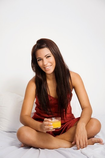 Brunette woman having an orange juice in bed : Stock Photo
