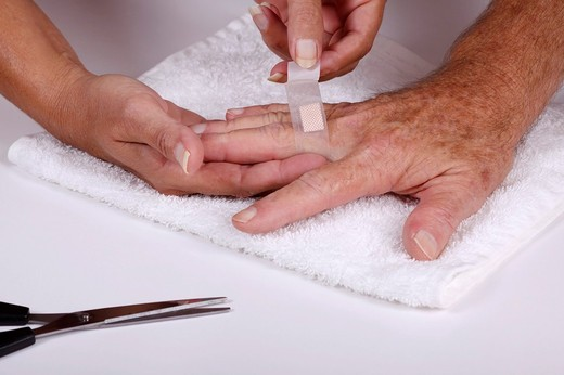 Stock Photo: 1566-682613 Woman applying a medical dressing to a man´s finger
