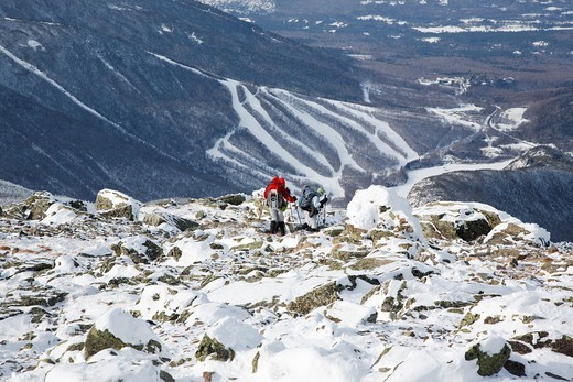 Stock Photo: 1566-682863 Three hikers descend from the summit of Mount Lafayette using the Greenleaf Trail during the winter months in the White Mountains, New Hampshire USA  Cannon Mountain ski area can be seen in the background