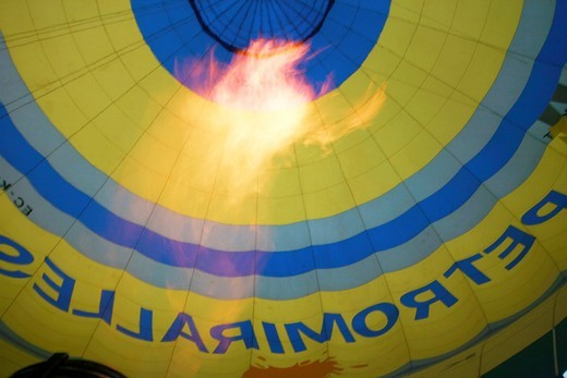 Stock Photo: 1566-683623 Flames of the burner inside the colourful envelope of a hot air ballon