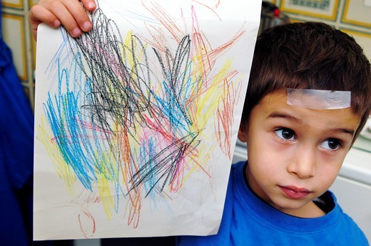 A child holding up his drawing : Stock Photo