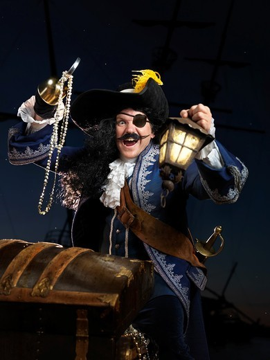 Stock Photo: 1566-685305 Pirate with a lantern opening a treasure chest