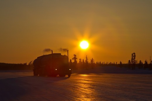Heavy trucks on the ice road from Tibbitt to Contwoyto beginning just outside of Yellowknife, Northwest Territories, Canada  MORE INFO This seasonal ice road is built through the lakes and ponds of the boreal forest in winter to allow heavy trucks to supp : Stock Photo