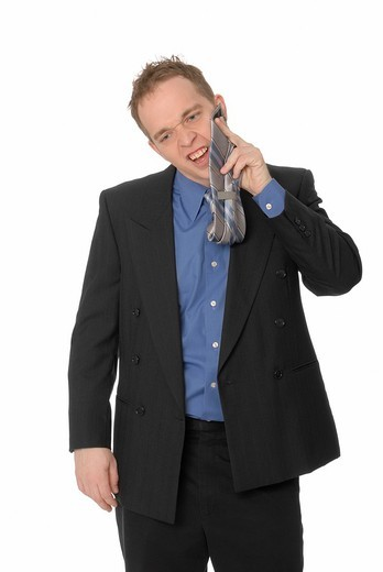 Business man wiping his face with his tie, nervous or bad manners : Stock Photo