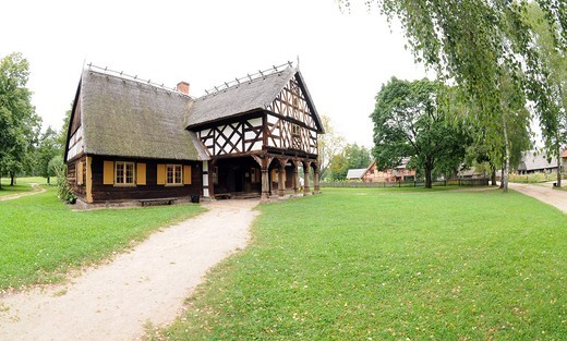 Replica of early 20th century hut with arcade extension, partly half-timbered wall and thatched roof from Masuria region, Poland : Stock Photo
