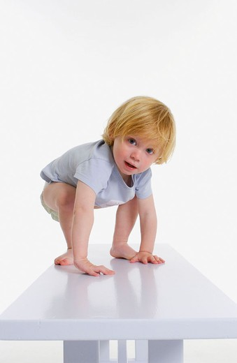 Toddler trying to stand on a bench : Stock Photo